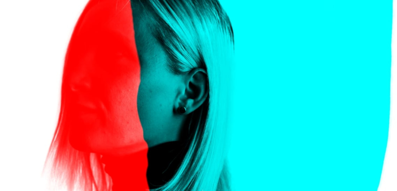 A photo of a blonde woman, whose face is obscured by bright red and blue color blocks.