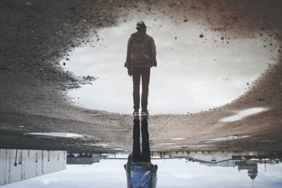 A man's reflection in a puddle shows him standing tall.