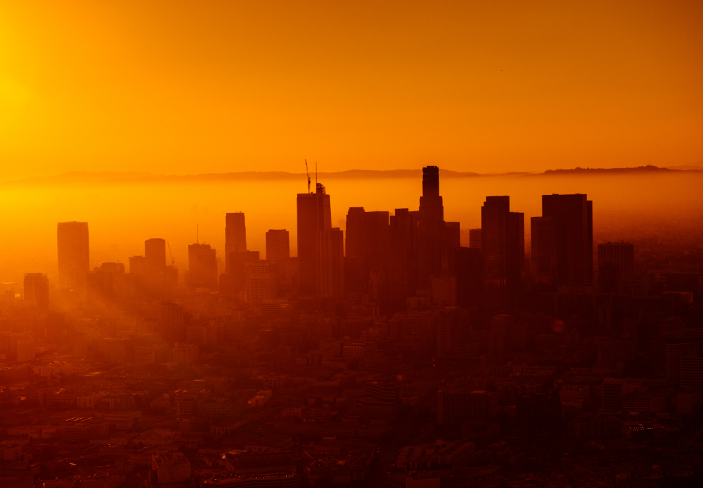 A city skyline is bathed in an orange sunset.