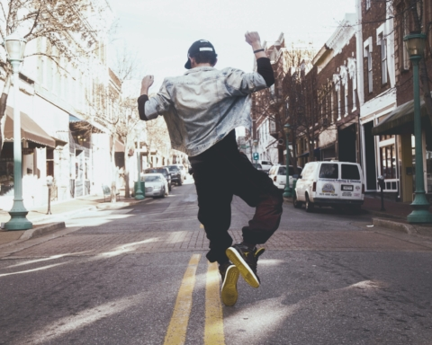 A man jumps in the street in joy.