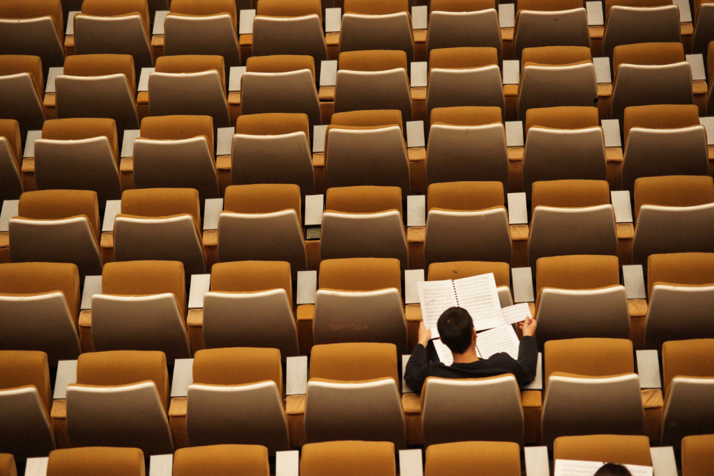 A university student reads his notes in an otherwise empty lecture hall.