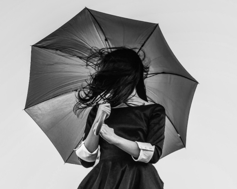 A woman in a dress holds up an umbrella, her hair in her face, in this photograph.
