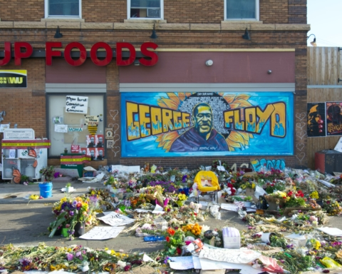 The George Floyd memorial at his place of death is strewn with flowers, notes, and a mural of his face and name.